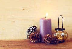 Vintage Lantern with burning Candle and pine cones on wooden table. filtered image. Royalty Free Stock Images