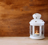 Vintage Lantern with burning Candle on wooden table. filtered image Royalty Free Stock Images