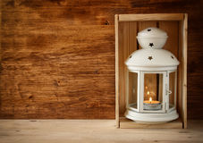 Vintage Lantern with burning Candle on wooden table. filtered image. Stock Photos