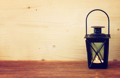 Vintage Lantern with burning Candle on wooden table. filtered image. Stock Photo
