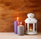 Vintage Lantern with burning Candle on wooden table. filtered image Stock Photography
