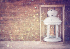 Vintage Lantern with burning candle on wooden table and glitter lights background. filtered image Royalty Free Stock Photography