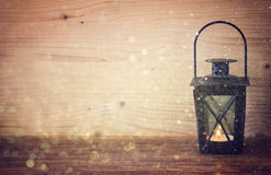 Vintage Lantern with burning candles, pine cones on wooden table and glitter lights background. filtered image Stock Photography