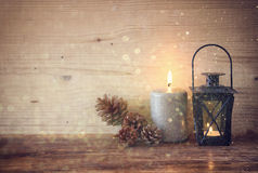 Vintage Lantern with burning candles, pine cones on wooden table and glitter lights background. filtered image Stock Images