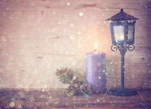 Vintage Lantern with burning candles, pine cones on wooden table and glitter lights background. filtered image. Stock Photography