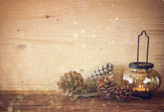 Vintage Lantern with burning candles, pine cones on wooden table and glitter lights background. filtered image Royalty Free Stock Photography
