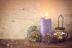 Vintage Lantern with burning candles, pine cones on wooden table and glitter lights background. filtered image. Royalty Free Stock Photos