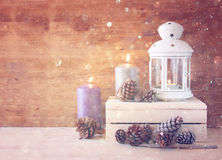 Vintage Lantern with burning candles, pine cones on wooden table and glitter lights background. filtered image Stock Photos