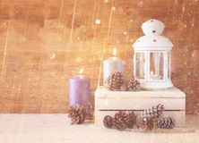 Vintage Lantern with burning candles, pine cones on wooden table and glitter lights background. filtered image. Royalty Free Stock Photography
