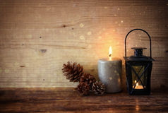 Vintage Lantern with burning candles, pine cones on wooden table and glitter lights background. filtered image.  Stock Photo