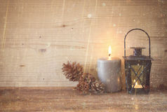 Vintage Lantern with burning candles, pine cones on wooden table and glitter lights background. filtered image. Stock Image