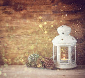 Vintage Lantern with burning candles, pine cones on wooden table and glitter lights background. filtered image Royalty Free Stock Photos