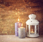 Vintage Lantern with burning candles on wooden table and glitter lights background. filtered image Royalty Free Stock Photo