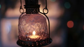 A vintage lantern with a candle on a background of Christmas lights stock video