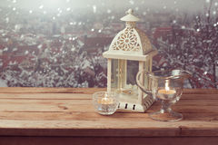 Vintage lantern with candles over winter town background with copy space Stock Photos
