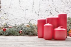 Vintage lantern red candles with Christmas fir tree garland on wooden board on window sill over nature snowing tree park backgroun stock photos