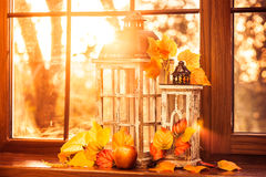 Vintage lanterns, autumn leaves and red apple in evening sun shi Royalty Free Stock Photos