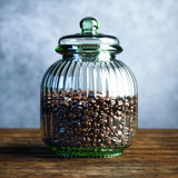 Vintage large glass vase filled with coffee beans on wood table Royalty Free Stock Image