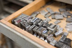 Vintage lead letterpress printing blocks against a weathered wooden drawer background with bokeh.  Stock Image