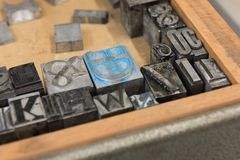 Vintage lead letterpress printing blocks against a weathered wooden drawer background with bokeh Stock Image