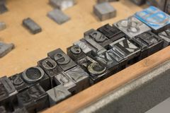 Vintage lead letterpress printing blocks against a weathered wooden drawer background with bokeh Stock Photos