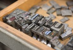 Vintage lead letterpress printing blocks against a weathered wooden drawer background with bokeh Royalty Free Stock Image