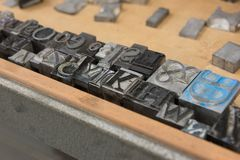 Vintage lead letterpress printing blocks against a weathered wooden drawer background with bokeh Royalty Free Stock Images