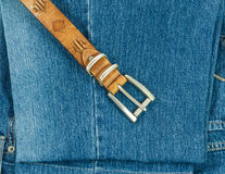Vintage leather belt with buckle on old blue jeans background Stock Photography