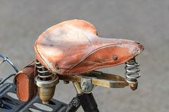 Vintage leather bike saddle with metal springs Stock Photos