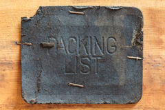Vintage leather packing list label. On a wooden background Royalty Free Stock Photos