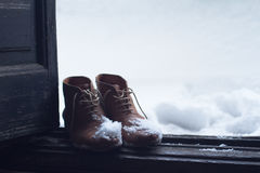 Vintage leather shoes covered in snow by the door stock image