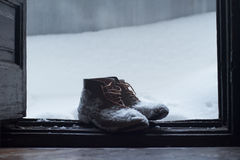 Vintage leather shoes covered in snow by the door stock photos