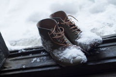 Vintage leather shoes covered in snow by the door stock photo