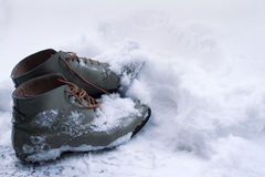 Vintage leather shoes covered in snow. Side view close up of a grey pair of vintage brown leather shoes covered in snow in winter time Royalty Free Stock Images
