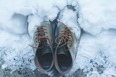 Vintage leather shoes covered in snow Royalty Free Stock Image