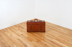 Vintage leather suitcase in empty room corner. Just arrived or leaving… Vintage leather suitcase in an empty corner of a room royalty free stock images