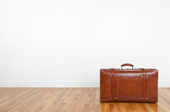 Vintage leather suitcase on a wooden floor. In an empty room Royalty Free Stock Photos