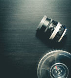 Vintage Lens with Movie Film roll on black background Stock Photos