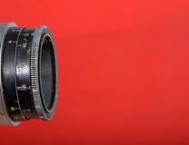 Vintage lens on red  background Royalty Free Stock Photography