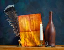 Old paper with a candle and a quill pen stock photo