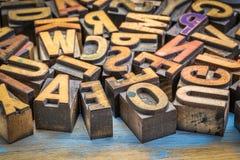 Vintage letterpress wood type printing blocks. Background of random vintage letterpress printing blocks on a grunge rustic wood Stock Images