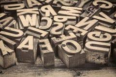Vintage letterpress wood type printing blocks. Background of random vintage letterpress printing blocks on a grunge rustic wood, sepia toned image Royalty Free Stock Image