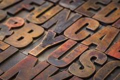 Vintage letterpress wood type printing blocks. Background of random vintage letterpress wood type printing blocks stained by color inks Stock Images