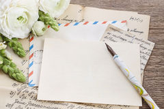 Vintage letters, ink and pen. White persian buttercup flowers Stock Photos