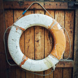Vintage Lifebuoy Hanging On A Rustic Wooden Wall With Copy Space. Retro lifebuoy on wooden wall background close up Royalty Free Stock Image