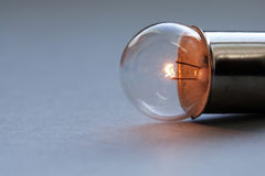 Vintage light bulb on gray background. Glowing filament close-up. Soft focus, copy space Royalty Free Stock Photo