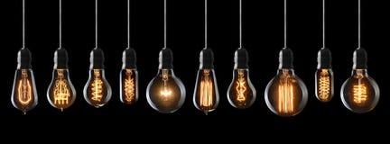 Vintage light bulbs. Set of vintage glowing light bulbs on black background Royalty Free Stock Photos