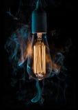 Vintage lightbulb. Surrounded with smoke Royalty Free Stock Image