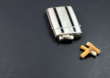 Vintage lighter/case and cigarette butts Royalty Free Stock Photography