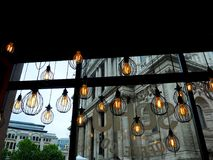Vintage Lights Hanging in a London Cafe. Vintage lights hanging in a British cafe overlooking St. Paul`s Cathedral in London royalty free stock image